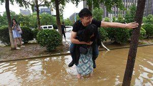 หญิงจีนต้องสตรอง !! ภาพสาวแบกแฟนหนุ่มลุยน้ำท่วมที่จีน