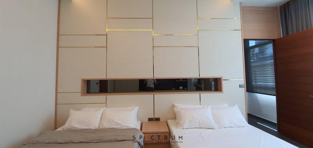 ผนังหัวเตียง กรุด้วยลามิเนตลายไม้ ตัดกับเส้นสแตนเลสสีทอง ตรงกลางทำเป็นช่องวางของหัวเตียงภายใน กรุกระจกเงาสีชา