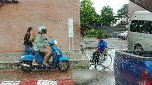 คนพิการจอดรถเข็นกลางสายฝน รอผู้ใช้ จยย. ลงจากทางเท้า ก่อนขึ้นไป
