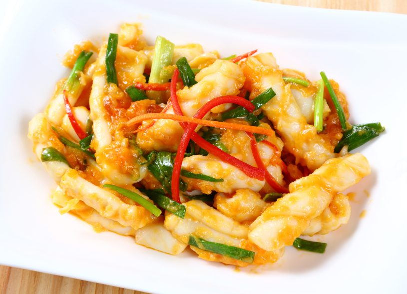 Close up stir fried squid with salted egg yolk on white dish